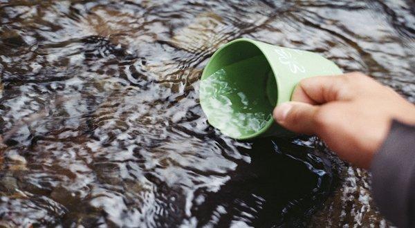 zielony kubek napełniany wodą ze strumienia