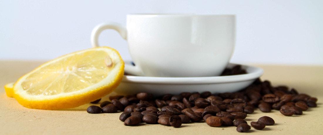 filiżanka z kawą obok cytryna i ziarna kawy